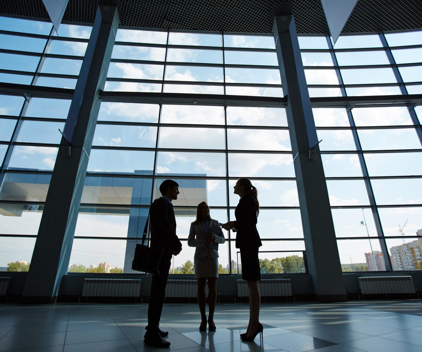 Three people standing in business center and talking